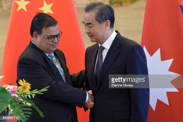 Deputy Prime Minister Of Nepal Krishna Bahadur Mahara shakes hands with Chinese Foreign Minister Wang Yi at the end of a joint press conference...