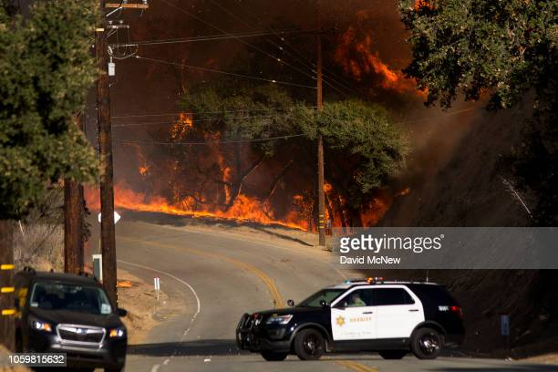 A deputy retreats from flames in Malibu Creek State Park during the Woolsey Fire on November 9 2018 near Malibu California After a experiencing a...