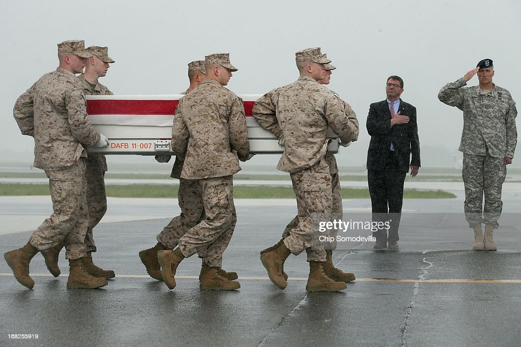 Deputy Secretary of Defense Ashton Carter (C) and Army Maj. Gen. William Rapp (R) salute as an Army carry team salutes, a U.S. Marine Corps carry team carries the flag-draped transfer case with the remains of Marine Staff Sgt. Eric Christian of Warwick, New York across the tarmac in the pouring rain at Dover Air Force Base May 7, 2013 in Dover, Delaware. Assigned to 2nd Marine Special Operations Battalion out of Camp Lejeune, North Carolina, Christian and one other Marine died May 4, while conducting combat operations in Farah province, Afghanistan.
