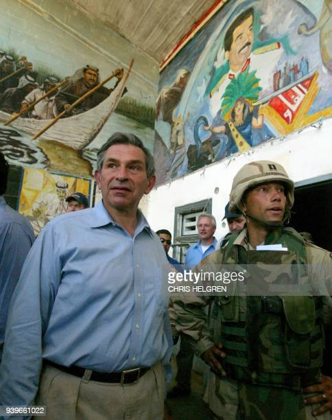 US Deputy Secretary of Defense Paul Wolfowitz scans murals of toppled Iraqi leader Saddam Hussein while touring Iraq's Abu Gharib prison on the...