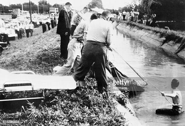 Deputy Sheriffs and volunteer workers remove the burlap wrapped body of 25yearold Irene Garza from an irrigation canal near the heart of McAllen Tex...