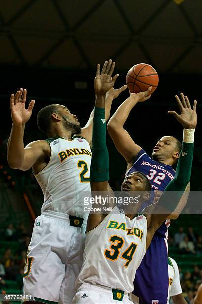 DeQuan Hicks of the Northwestern State Demons shoots the ball over Rico Gathers and Cory Jefferson of the Baylor Bears on December 18 2013 at the...