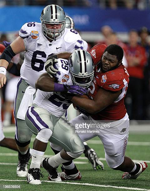 DeQuinta Jones of the Arkansas Razorbacks makes a tackle after losing his helmet against Angelo Pease of the Kansas State Wildcats during the Cotton...