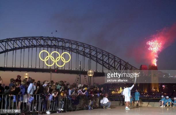 Der australische TennisStar Patrick Rafter läuft am mit dem olympischen Feuer in der Hand vor der Harbour Bridge vorbei einem der Wahrzeichen von...