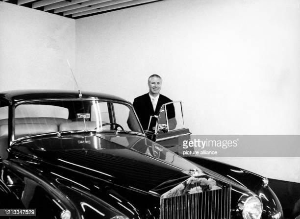 Der Autohändler Wilhelm Becker steht nach der Eröffnung seines ersten Autosupermarkt der Welt in Düsseldorf am neben dem teuersten Wagen seines...