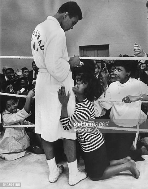 Der Boxer Muhammad Ali gibt aus dem Boxring heraus Autogramme an weibliche Fans ohne Jahr