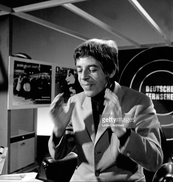 """Der britische Sänger, Schauspieler, Radiomoderator und Fernsehmoderator Chris Howland mit einer Perücke bei Aufnahmen für seine TV Sendung """"Musik aus..."""
