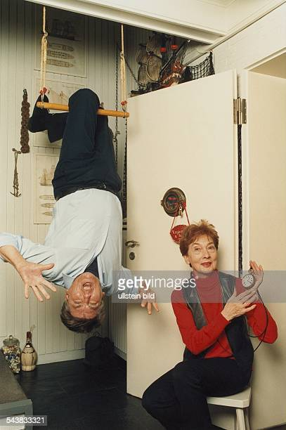 Der deutsche Artist Sensationsdarsteller und Stuntman Arnim Dahl hängt kopfüber an einem Schaukelreck in seiner Wohnung Seine Ehefrau Regina sitzt...
