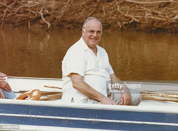 Der deutsche Bundeskanzler Helmut Kohl sitzt im kurzärmeligen Hemd in einem Boot das auf einem schlammigen Fluss fährt Undatiertes Foto