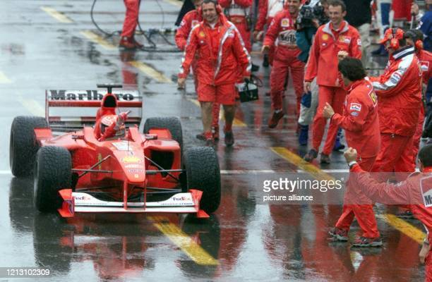 Der deutsche Ferrari Formel-1-Pilot Michael Schumacher jubelt am in Montreal nach seinem Sieg im Großen Preis von Kanada seinen Mechanikern zu.