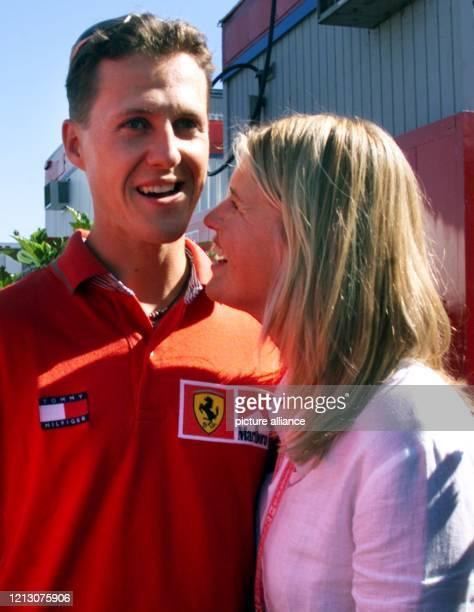 Der deutsche Ferrari-Formel 1-Pilot Michael Schumacher lacht am zusammen mit Ehefrau Corinna im Fahrerlager der Rennstrecke Gilles Villeneuve in...
