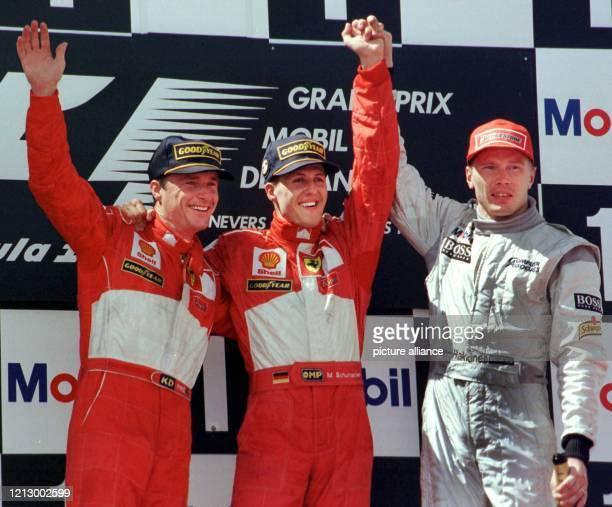 Der deutsche FerrariPilot Michael Schumacher jubelt am 2861998 nach seinem Sieg beim Großen Preis von Frankreich in auf der Formel 1Rennstrecke in...