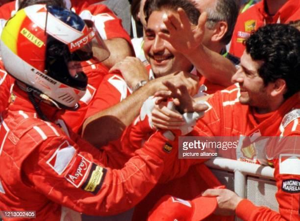 Der deutsche Formel 1Pilot Michael Schumacher jubelt nach seinem Sieg am 2861998 beim Großen Preis von Frankreich in MagnyCours mit seinem Boxenteam...
