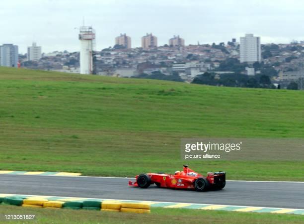 Der deutsche Formel 1Pilot Michael Schumacher rast am in seinem Ferrari vor der Stadtsilhouette von Sao Paulo entlang Im Qualifikationstraining zum...