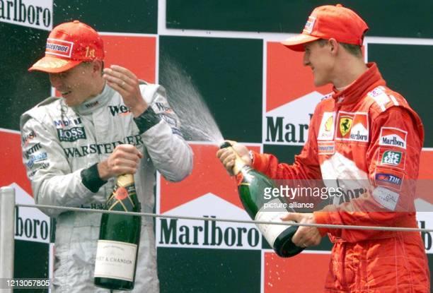 Der deutsche Formel 1-Pilot Michael Schumacher spritzt am den Sieger des Großen Preises von Spanien, Mika Häkkinen, am Ciruit de Catalunya in...