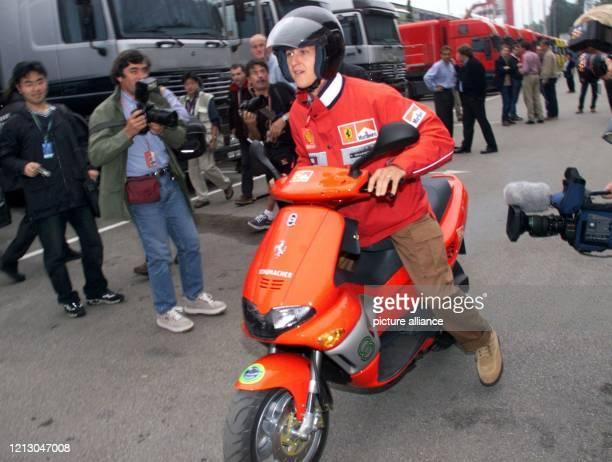 Der deutsche Formel 1-Vizeweltmeister Michael Schumacher versucht sich am 29.4.1999 mit seinem neuen Motorroller durch das Fahrerlager der...