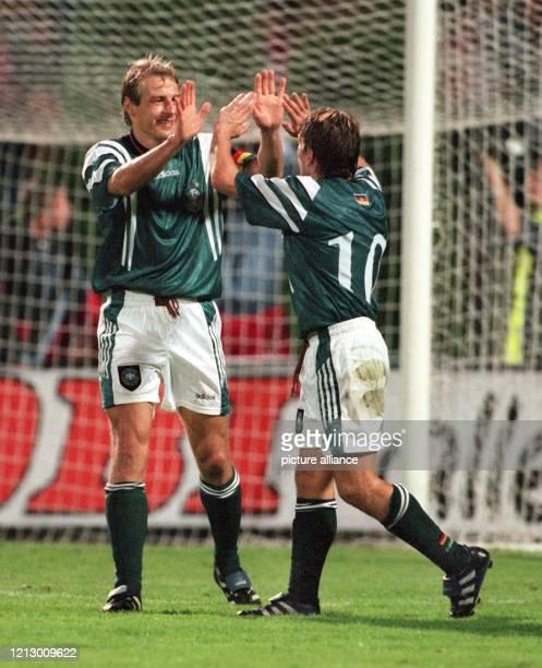 Der deutsche Fußball-Nationalspieler Jürgen Klinsmann freut sich während der Länderspiel-Partie Polen - Deutschland in Zabrze am zusammen mit Thomas...