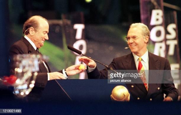 Der deutsche FußballWeltmeister und WeltmeisterTrainer Franz Beckenbauer reicht Joseph Blatter dem Schweizer Generalsekretär des Weltfußballverbandes...