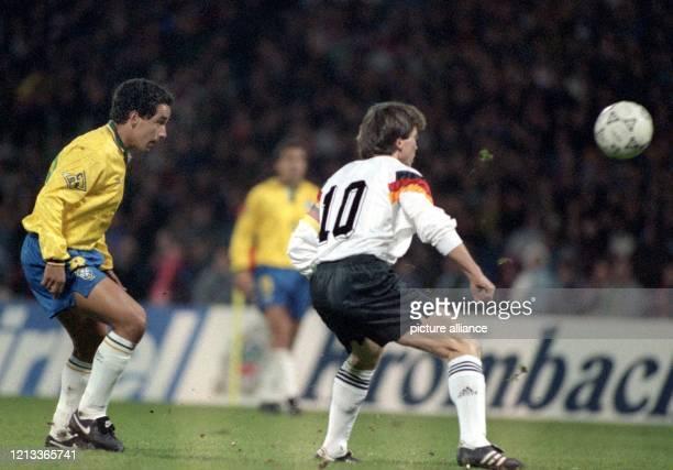 Der deutsche Mittelfeldspieler Lothar Matthäus steht näher zum Ball als der brasilianische Mittelfeldakteur Zinho. Die deutsche...