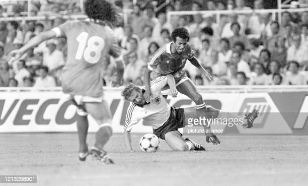 Der deutsche Mittelfeldspieler Wolfgang Dremmler kommt im verbissenen Zweikampf mit dem französischen Mittelfeldakteur Jean Tigana zu Fall Dessen...