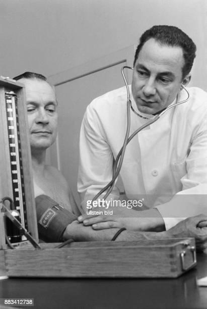 Der deutsche Musiker Dr Abbi Hübner Chef der Hamburger JazzBand 'Abbi Hübner his Low Down Wizards' ist Arzt Hier misst er im weißen Kittel einem...