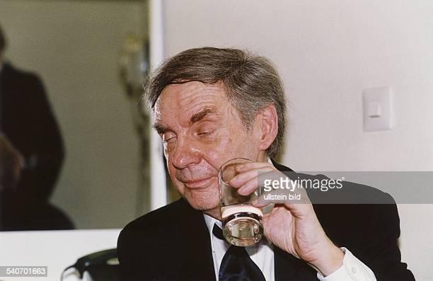 Der deutsche Schauspieler und Entertainer Harald Juhnke hält ein Glas mit Alkohol in der Hand