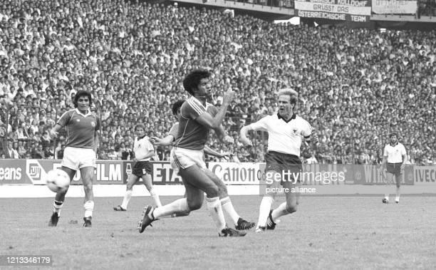 Der deutsche Stürmer Karl-Heinz Rummenigge kommt vor den chilenischen Abwehrspielern Rodolfo Dubo und Rene Eduardo Valenzuela zum Torschuß. Die...