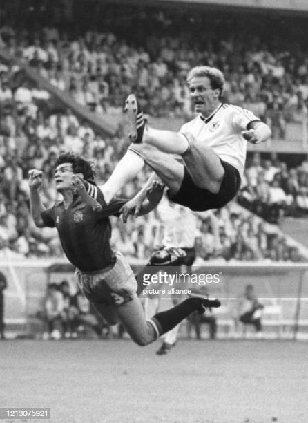 Der deutsche Stürmer Karl-Heinz Rummenigge liefert sich einen Zweikampf mit dem spanischen Abwehrspieler Jose Antonio Camacho und fällt dabei auf den...