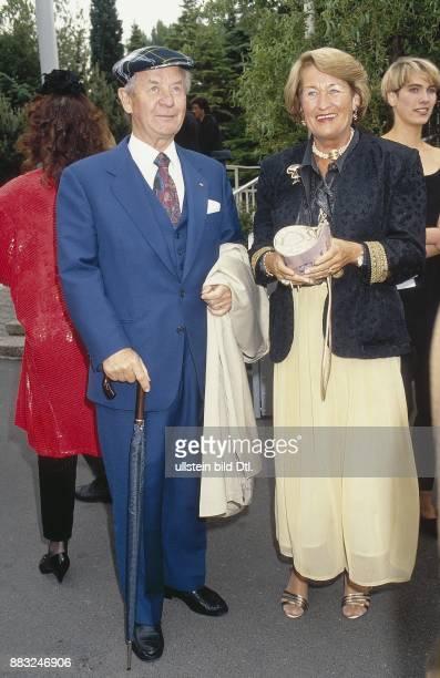 Der deutsche Verleger Gustav Heinrich Lübbe steht auf einen Regenschirm gestützt neben seiner Frau Ursula die mit beiden Händen ihre Handtasche hält...