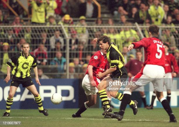 Der Dortmunder Mittelfeldspieler Andreas Möller dribbelt sich durch die Abwehr von Manchester United Gary Pallister und Ronny Johnsen können ihn...