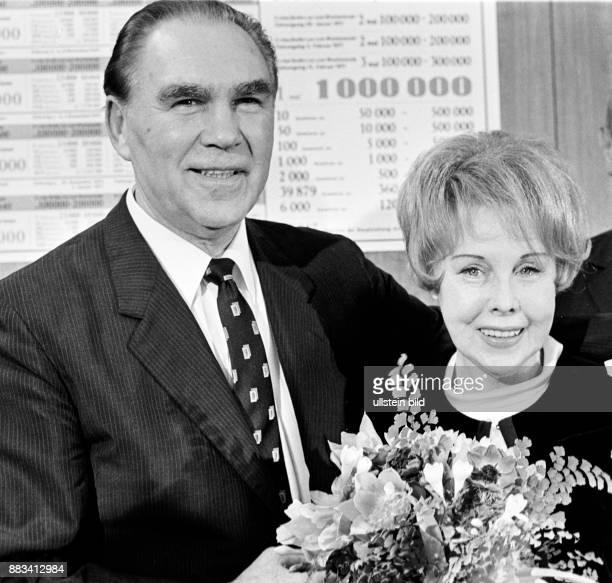 Der ehemalige Boxprofi und Unternehmer Max Schmeling mit seiner Frau der Schauspielerin Anny Ondra Sie hat einen Blumenstrauß in der Hand
