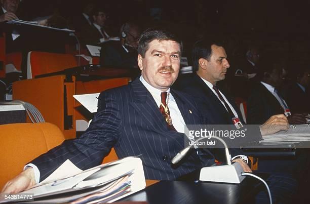 Der ehemalige Fechter Thomas Bach ist seit 1991 Mitglied des Internationalen Olympischen Komitees Er befindet sich in einem Sitzungssaal vor sich ein...