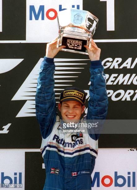 Der Formel 1Rennfahrer Jacques Villeneuve reckt am 2291996 jubelnd seinen beim Großen Preis von Portugal gewonnenen Pokal in die Höhe Es war bereits...