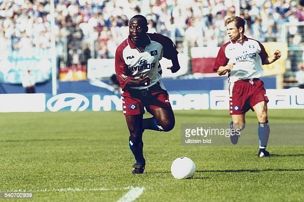 Der Fußballspieler Anthony Yeboah vom Hamburger SV führt den Ball Aufgenommen September 1999
