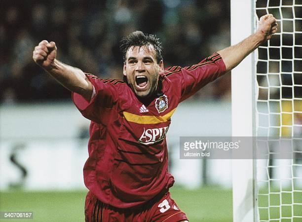 Der Fußballspieler Ulf Kirsten von Bayer Leverkusen reißt jubelnd die Arme in die Höhe