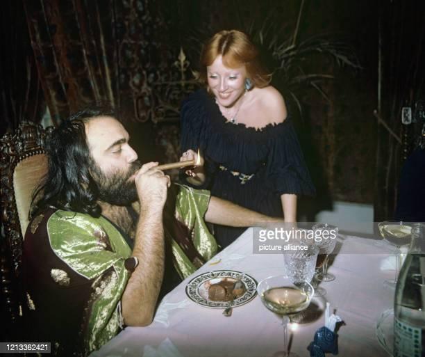 Der griechische Schlagersänger Demis Roussos , lässt sich im Esszimmer von seiner Ehefrau Dominique eine Zigarre anzünden, aufgenommen im November...