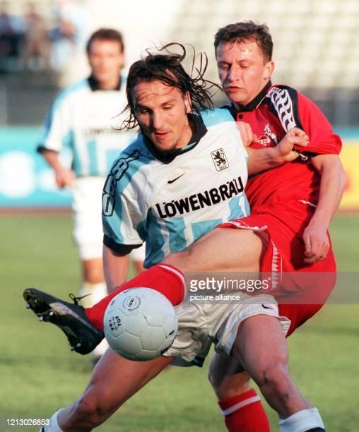 Der Kölner Mittelfeldspieler Dorinel Munteanu klammert am 2221997 im Auswärtsspiel bei 1860 München deren Mittelfeldakteur Jens Jeremies In der 21...