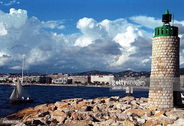 Der Leuchtturm auf einer aus Felsen künstlich angelegten Mole an der Hafeneinfahrt von Cannes Im Hintergrund sind die Gebäude am Boulevard de la...