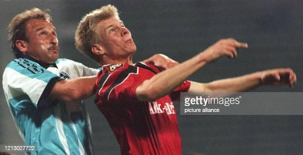Der Münchner 1860-Abwehrspieler Thomas Miller und Leverkusens Angreifer Markus Feldhoff springen synchron hoch in Erwartung des Balles. 1860 München...