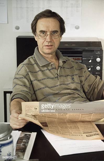 """Der Moderator und Journalist Wolf von Lojewski sitzt mit der """"Financial Times"""" in den Händen an einem Tisch, hinter sich eine Stereoanlage...."""