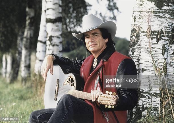 Der Musiker Tom Astor sitzt mit einer Gitarre auf dem Schoß an einem Birkenstamm gelehnt Er trägt einen Cowboyhut und für Countrymusik typische...
