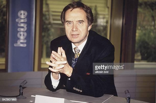 """Der Nachrichtensprecher Wolf von Lojewski sitzt im """"Heute Journal""""-Studio mit verschränkten Händen an einem Schreibtisch, auf dem sich zwei kleine..."""