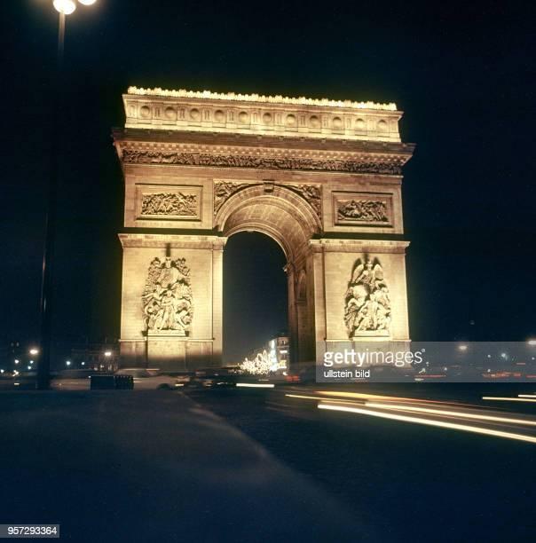 Der Pariser Triumphbogen am Place CharlesdeGaulle wird nachts beleuchtet aufgenommen im November 1970 in Paris Der Triumphbogen wurde 1806 von...