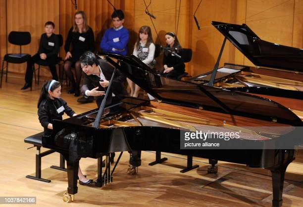 Der Pianist Lang Lang steht neben der siebenjährigen USamerikanischen Pianistin Avery Lin Gagliano die am in München in der Hochschule für Musik und...