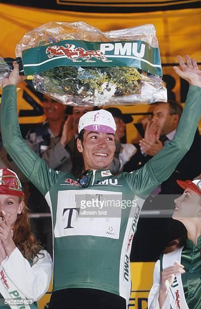 Der Radrennfahrer Erik Zabel hebt als Etappensieger bei der Tour de France 1997 im Telekomdress jubelnd einen Blumenstrauß hoch. Aufgenommen 1997.