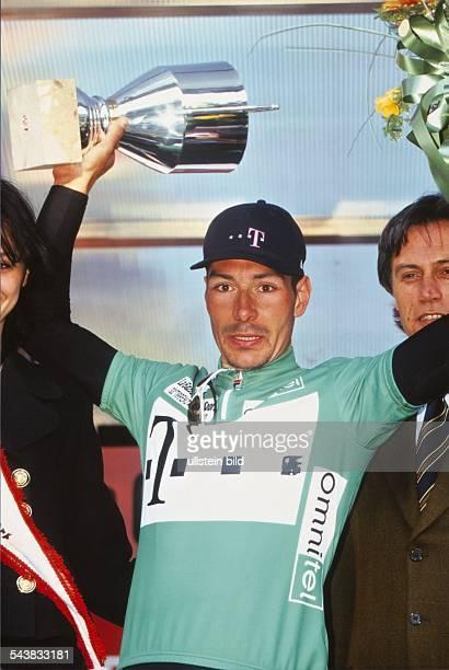 Der Radrennfahrer Erik Zabel im grünen Telekomtrikot schwenkt einen Pokal. Undatiertes Foto.