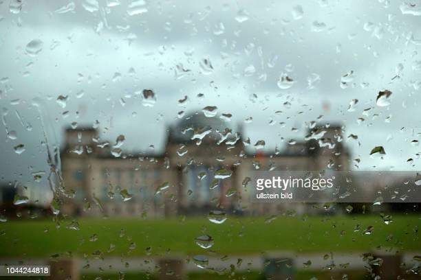 Der Reichstag hinter einer Glasscheibe mit Regentropfen