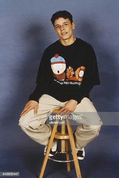Der Schauspieler David Lütgenhorst sitzt auf einem Hocker Aufgenommen Dezember 1999