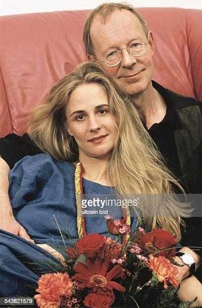 Der Schauspieler Hans-Peter Korff sitzt auf dem Sofa und hält seine Ehefrau Christiane in den Armen. Vor ihnen ein Blumenstrauß. Undatiertes Foto.