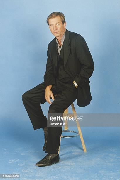 Der Schauspieler Michael Lesch sitzt auf einem Hocker und hat eine Hand in der Hosentasche Aufgenommen November 1998